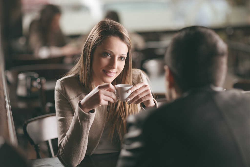 A woman holding coffee and gazing at a man
